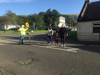 Lollipop lady helping with crossing