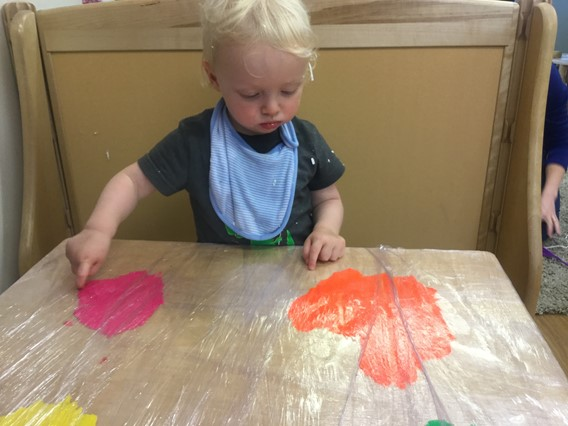 child at table finger painting