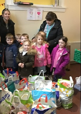 CHILDREN AND PARENTS WITH FOOD BAG COLLECTIONS