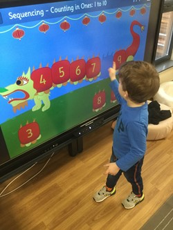 child at screen pointing to missing number