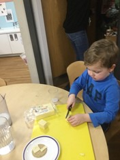child at table cutting cheese