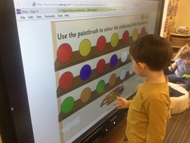 child at board with colour palate